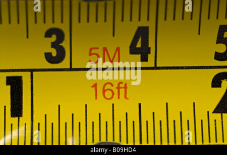 Stock photo of a tape measure showing both the metric and imperial measurements - Stock Photo