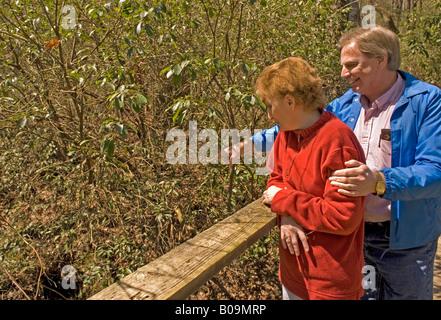 Caucasian Couple (50-55) Look Over Bridge on Trail at Davidson River Campground Near Brevard North Carolina USA - Stock Photo