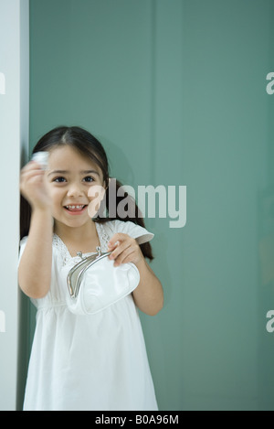 Little girl holding coin purse, one hand raised, smiling - Stock Photo