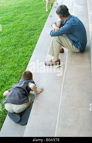 Grandfather and grandchildren sitting on steps, playing with toy cars, high angle view - Stock Photo