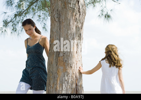 Two sisters walking around tree trunk, little girl touching tree with hand - Stock Photo