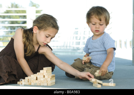 Brother and sister sitting on the ground, playing with building blocks together - Stock Photo
