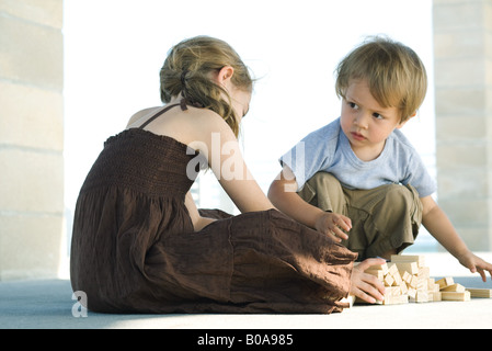 Boy and girl sitting on floor, playing with building blocks - Stock Photo