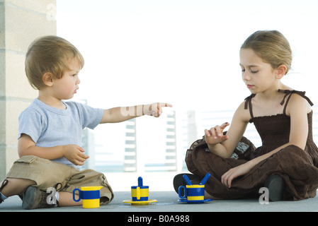 Siblings sitting on the ground together, brother pointing a sister, sister looking down at finger - Stock Photo
