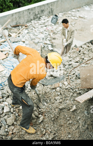 Construction worker digging at construction site, high angle view - Stock Photo