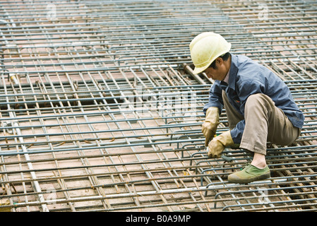 Man crouching at construction site, building steel framework - Stock Photo