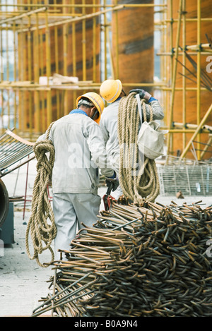 Workers at construction site carrying rope, metal rods stacked in foreground - Stock Photo
