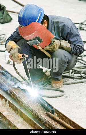 Worker welding metal rod at construction site, close-up - Stock Photo