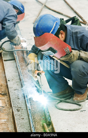 Worker using welding torch at construction site, side view - Stock Photo