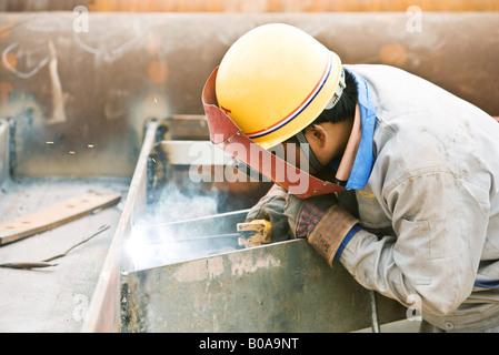 Welder working, side view - Stock Photo