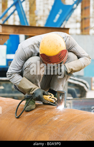 Welder crouching on metal pipe, head down - Stock Photo
