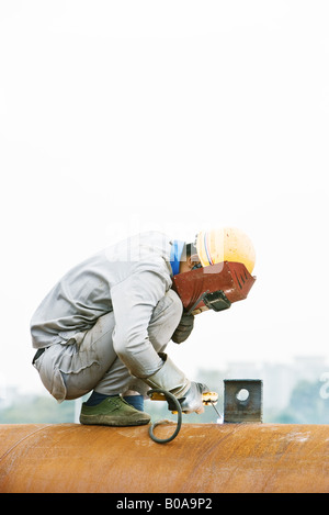 Welder crouching on metal pipe, looking down, side view - Stock Photo