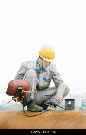 Worker crouching on metal pipe, holding welding mask, looking down - Stock Photo