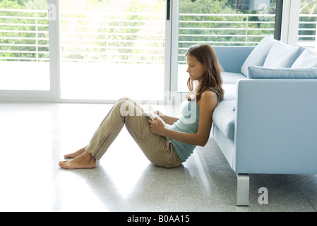 Teenage girl sitting on the ground, leaning against sofa, reading book, side view - Stock Photo