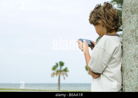 Boy leaning against tree trunk, playing handheld video game, side view - Stock Photo