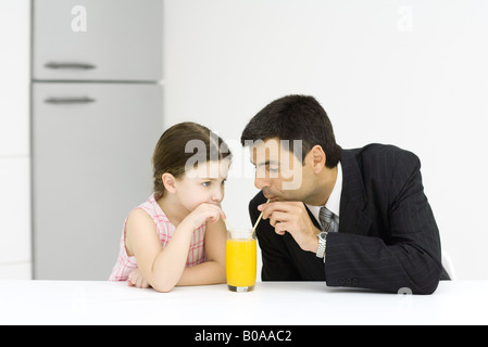 Little girl and father drinking from glass of juice together - Stock Photo