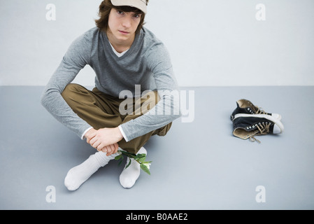 Young man sitting on the ground next to his shoes, holding flower, looking at camera - Stock Photo