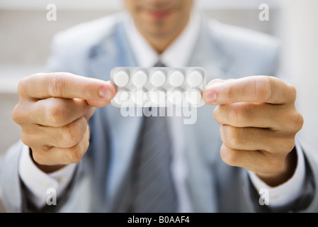 Businessman holding out medicine in blister pack, focus on foreground, cropped view - Stock Photo