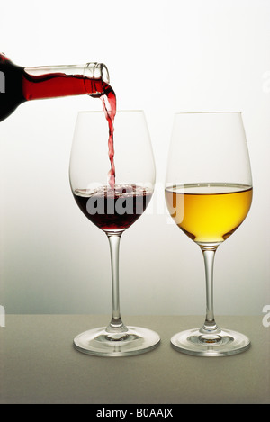 Two wine glasses, red wine being poured into one, white wine in the other - Stock Photo