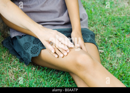 Female sitting on the ground, holding woman's hand, cropped view - Stock Photo