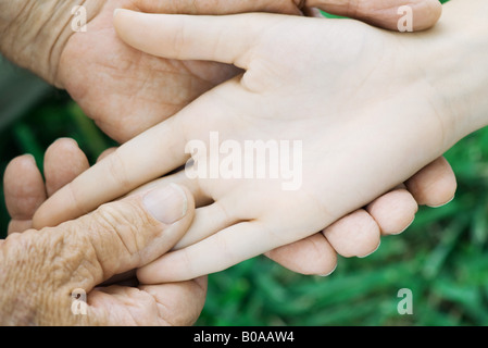 Elderly man holding female's hand, close-up, cropped view - Stock Photo