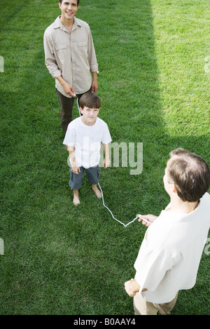 Boy playing jump rope with two men, smiling at camera - Stock Photo