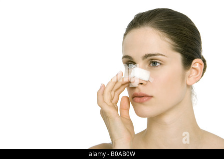 Young woman with bandage on nose, looking away - Stock Photo