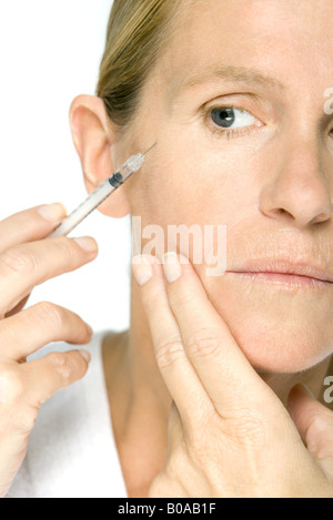 Woman receiving Botox injection, cropped view - Stock Photo