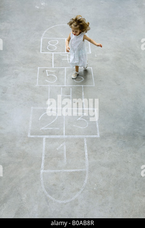 Little girl playing hopscotch, high angle view - Stock Photo