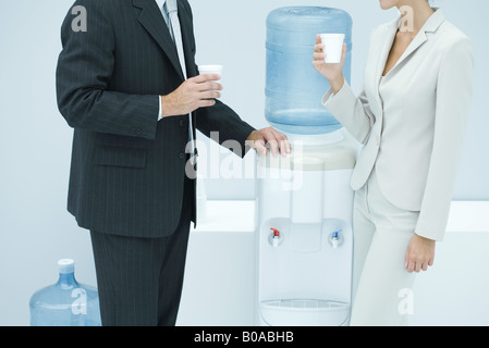 Two business colleagues standing by water cooler, cropped - Stock Photo