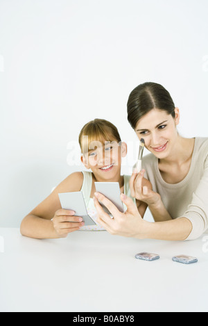Young woman sitting next to preteen sister, putting on make-up, both looking into hand mirrors - Stock Photo