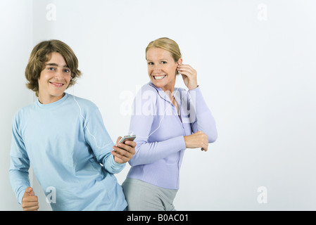 Mother and teen son listening to MP3 player together, dancing, smiling at camera - Stock Photo