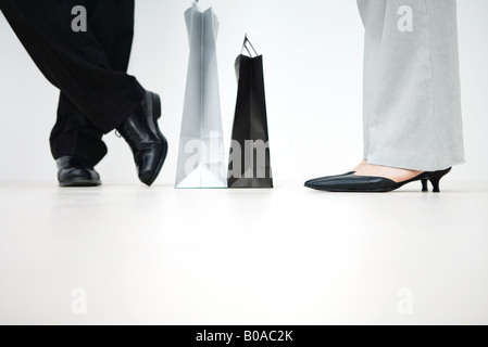 Couple standing with shopping bags between them, cropped view of feet, low angle view - Stock Photo