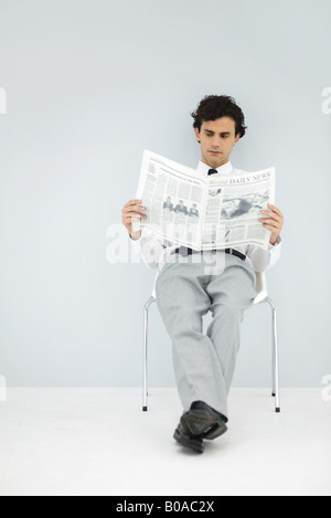 Businessman slouching in chair, reading newspaper - Stock Photo