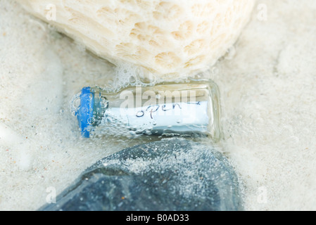 Bottle containing message in shallow water, close-up - Stock Photo