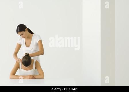Massage therapist massaging woman's back - Stock Photo