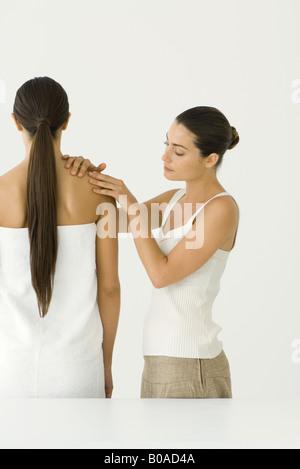 Massage therapist giving woman a shoulder massage - Stock Photo