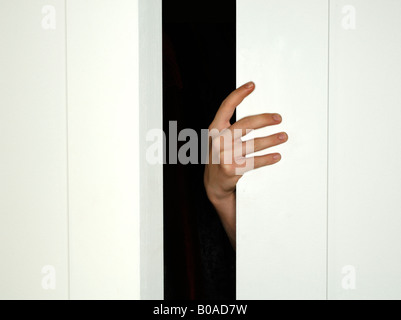 A hand holding open closed a white door - Stock Photo