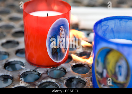 Burning candle offerings by pilgrims to Lourdes, France. - Stock Photo