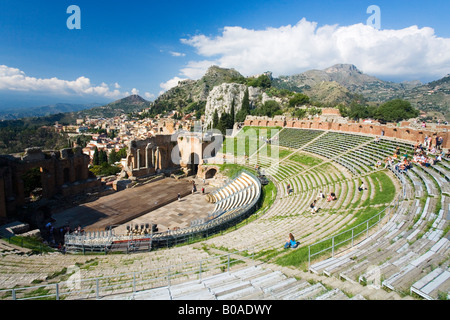 Greek Greco Roman Theatre Theater amphitheater ruined amphitheatre in summer sunshine with town of Taormina Island Sicily