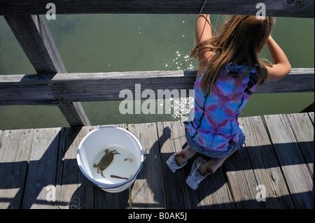 Young girl crab fishing from pier at Hunting Island South Carolina, USA. - Stock Photo
