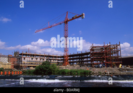 crane on construction site of Merchants Quay apartments by the River Aire Leeds Yorkshire UK - Stock Photo