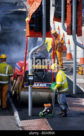 construction workers doing resurfacing work at roadworks in Leeds Yorkshire UK - Stock Photo