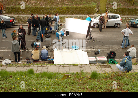 Outdoor film set film crew actors and technical staff on location in public park - Stock Photo