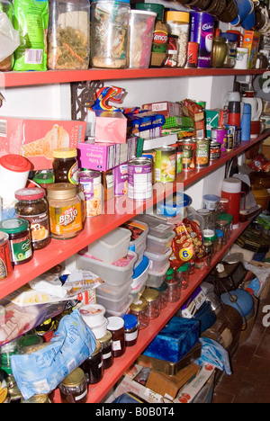 Untidy Larder full of tins of food and hoarded items - Stock Photo