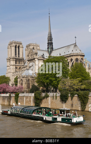 Notre Dame cathedral in Paris with a tourist boat on the River Seine. - Stock Photo