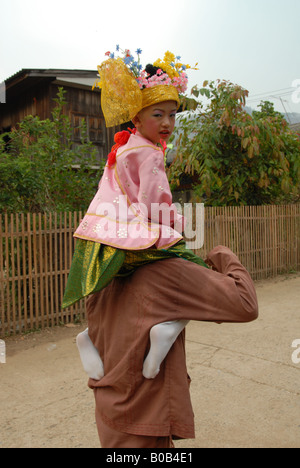 little boy is sitting on his relative shoulder, head to the temple during poi sang long festival in mae hong son - Stock Photo