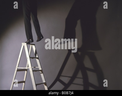 man precariously on ladder - Stock Photo