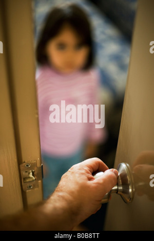Man's hand on the doorhandle with a four year old girl inside the room - Stock Photo