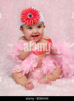 little Hispanic girl sitting and dressed in pink with sunglasses and flower hat